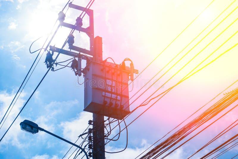 Polo y línea eléctrica de alto voltaje de la electricidad del transformador con el fondo azul de cielo nublado imágenes de archivo libres de regalías