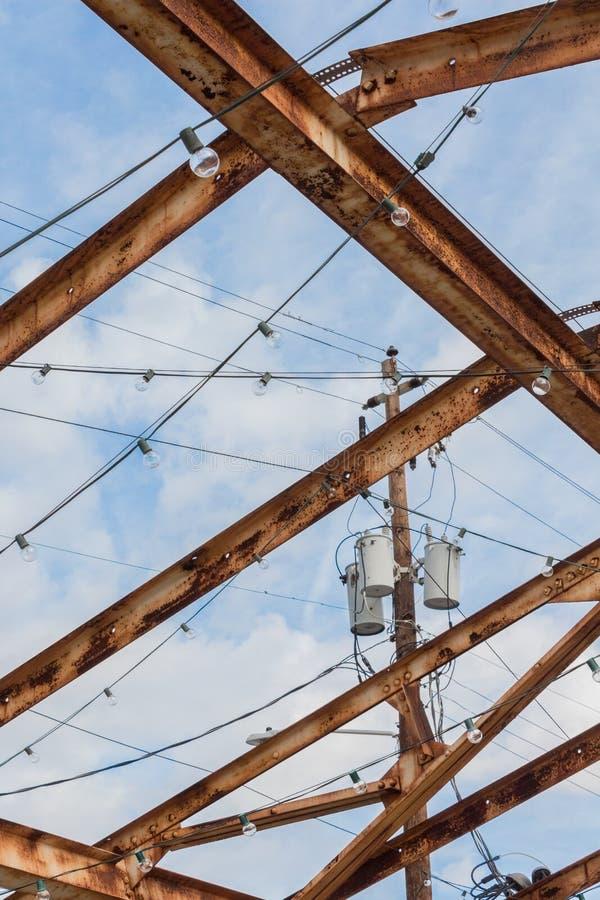 Polo y transformadores de poder fijados contra un cielo azul, sistema a través aherrumbrado visto del tejado de la viga imágenes de archivo libres de regalías