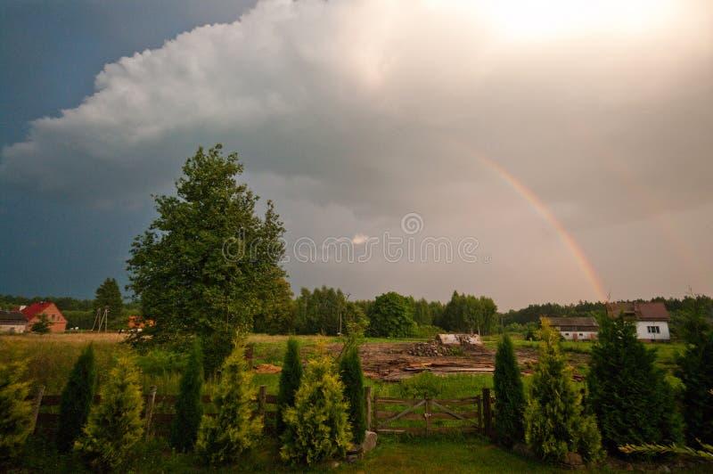 Polonia rural, región de Ilawa, arco iris sobre el pueblo de Sapy imágenes de archivo libres de regalías