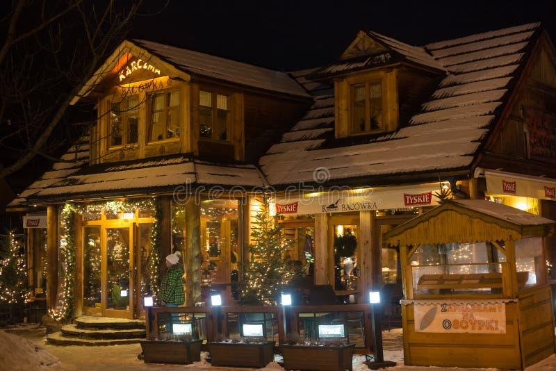 POLONIA, ZAKOPANE - 3 DE ENERO DE 2015: Restaurante de madera tradicional en la calle en Zakopane en la decoración de la Navidad imagen de archivo