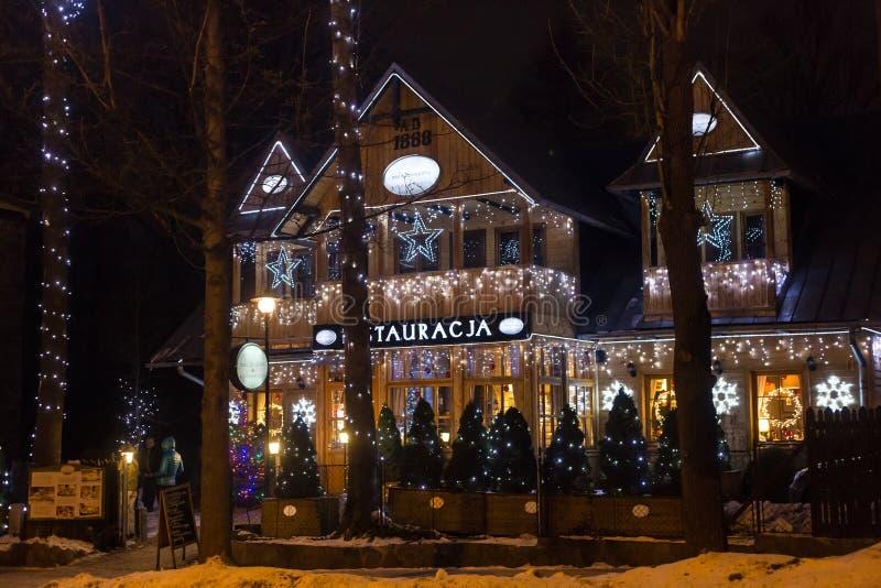 POLONIA, ZAKOPANE - 3 DE ENERO DE 2015: Restaurante de madera tradicional en la calle en Zakopane en la decoración de la Navidad imagenes de archivo