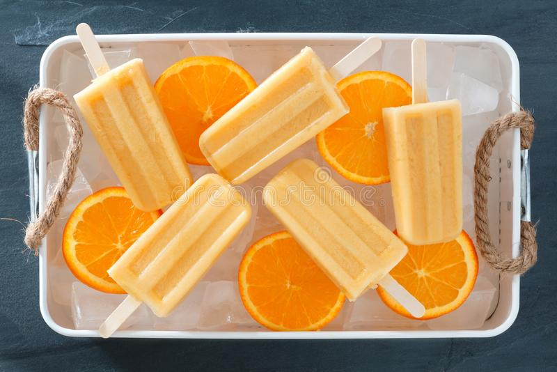 Polos anaranjados hechos en casa en una bandeja de hielo rústica fotos de archivo