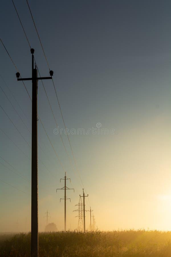 Polos com fios de alta tensão são iluminados pelo sol do alvorecer no campo da criação do tema da infinidade fotografia de stock royalty free
