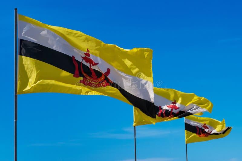 polos de bandeiras de Brunei Darussalam Darussalam em fundos do céu fotos de stock royalty free
