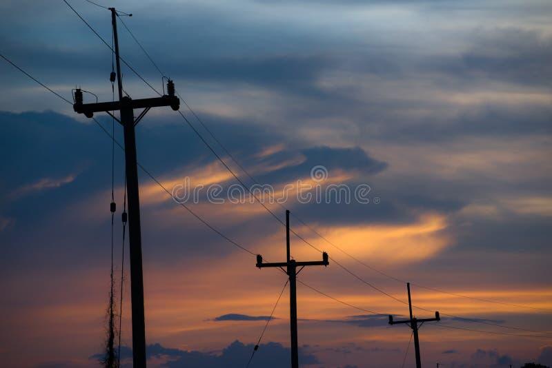 Polos de la electricidad en el cielo colorido, puesta del sol imagen de archivo