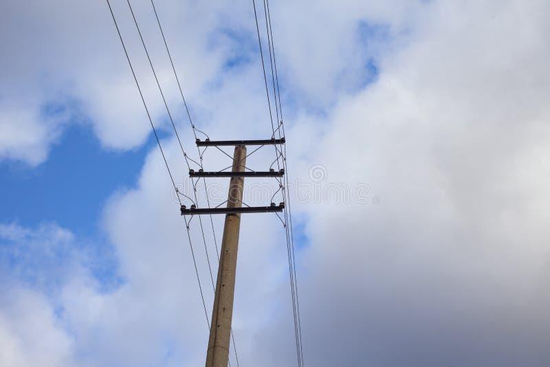Polos de la línea eléctrica contra el cielo con las nubes imágenes de archivo libres de regalías