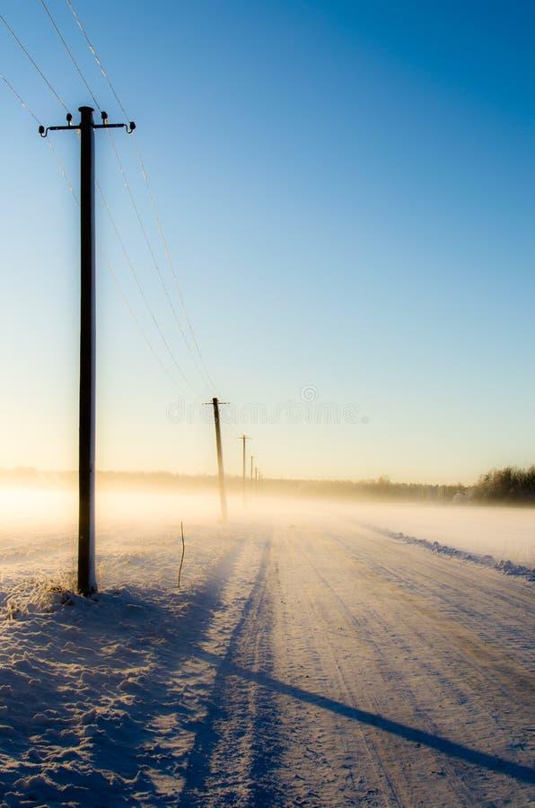 Polos de teléfono en un camino de niebla de la nieve imagenes de archivo