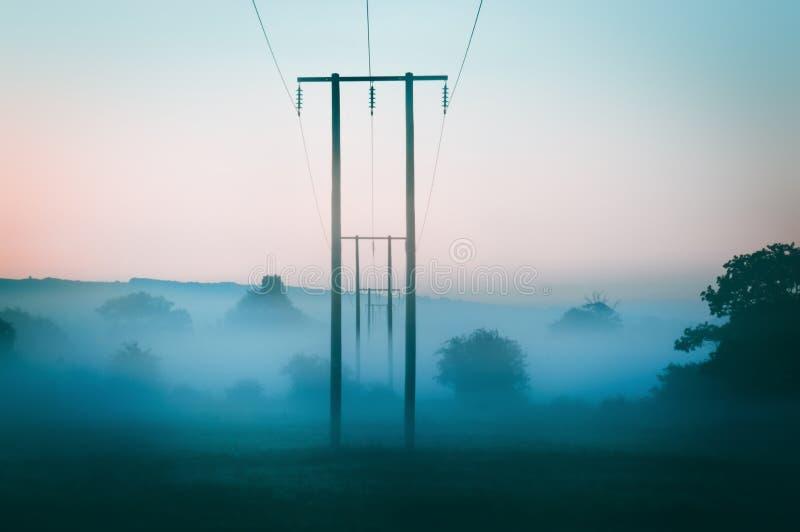Polos de telégrafo que entram na distância em uma manhã enevoada imediatamente antes do nascer do sol no campo inglês foto de stock royalty free