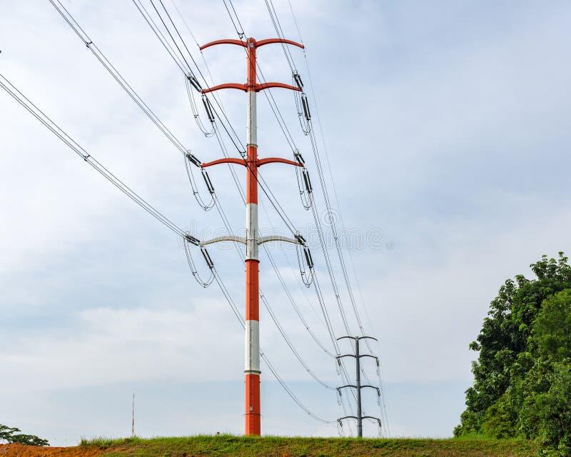 Polos eléctricos con los alambres contra el cielo, línea eléctrica foto de archivo