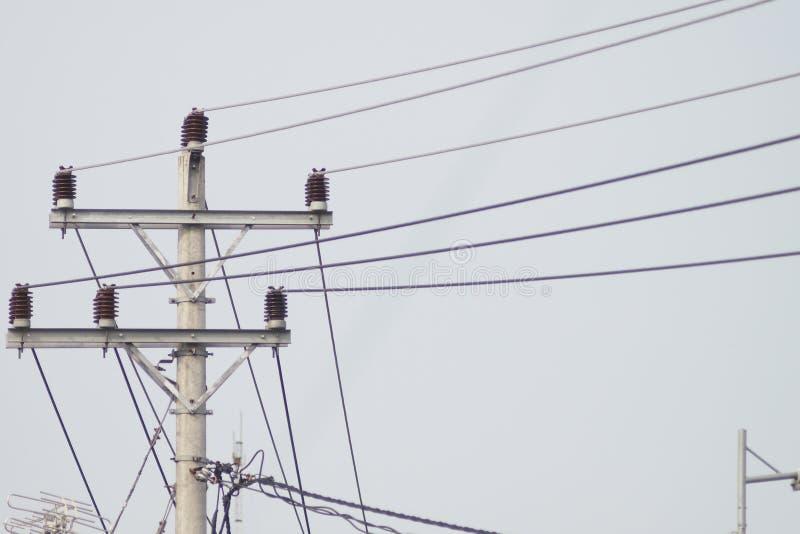 Polos eléctricos del cable y del cielo fotografía de archivo