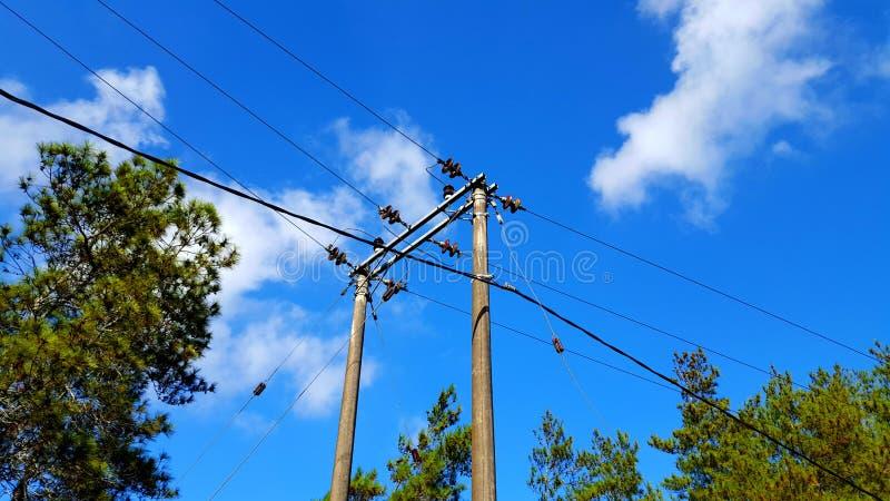 Polos elétricos com cabos, distribuição da eletricidade às casas e propriedades industriais fotos de stock royalty free