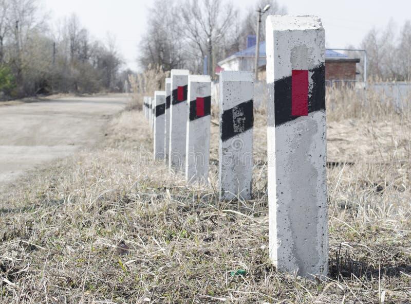 Polos listrados perto do cruzamento de estrada de ferro Limite de velocidade segurança Um aviso foto de stock