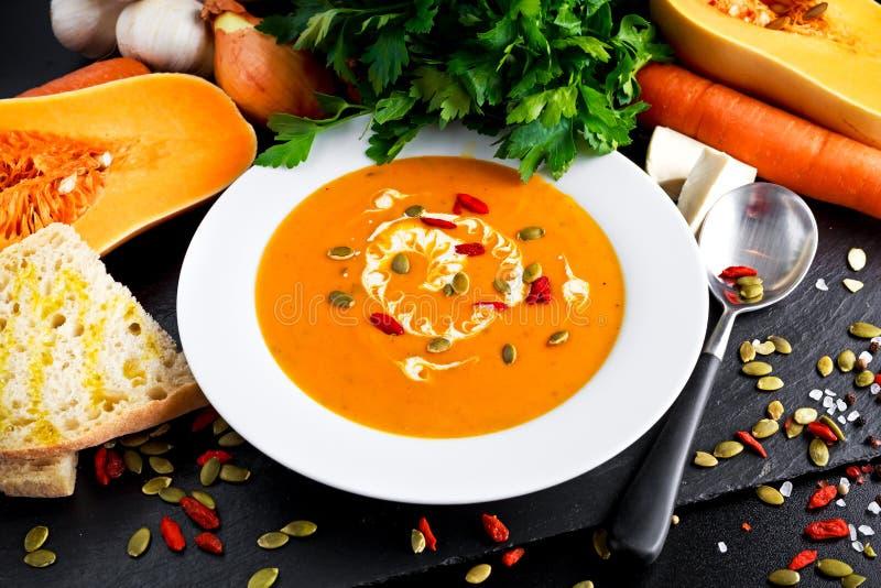Polpa de butternut e sopa lisas da cenoura com creme, bagas do goji das sementes de abóbora fotos de stock