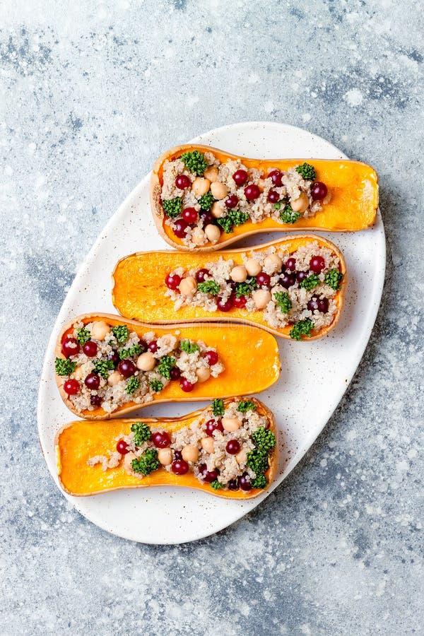 A polpa de butternut enchida com grãos-de-bico, arandos, quinoa cozinhou na noz-moscada, cravos-da-índia, canela Receita do janta foto de stock