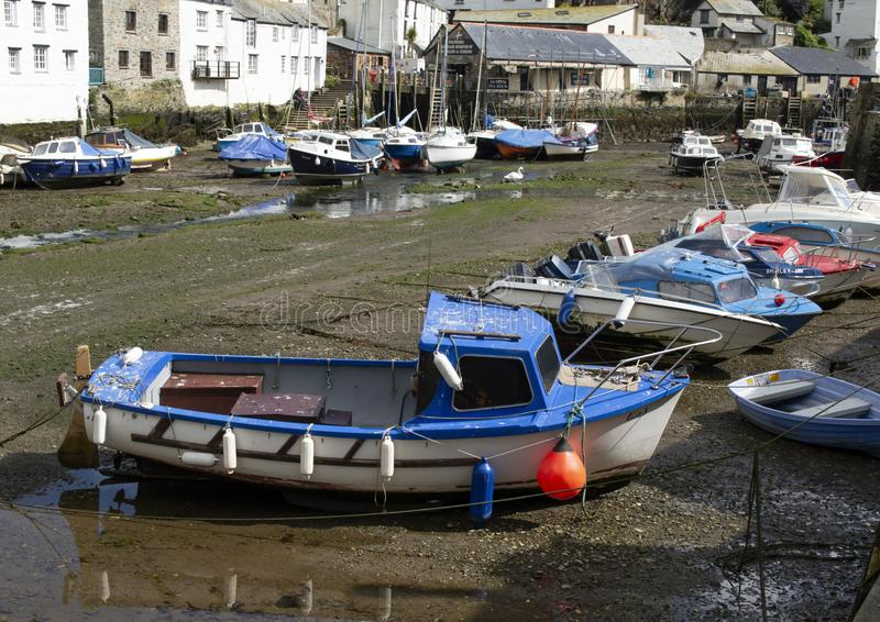 Polperro harbour collection of small boats and yachts in dry basin with buildings in background. Cornwall Polperro harbour collection of small boats and yachts royalty free stock photography