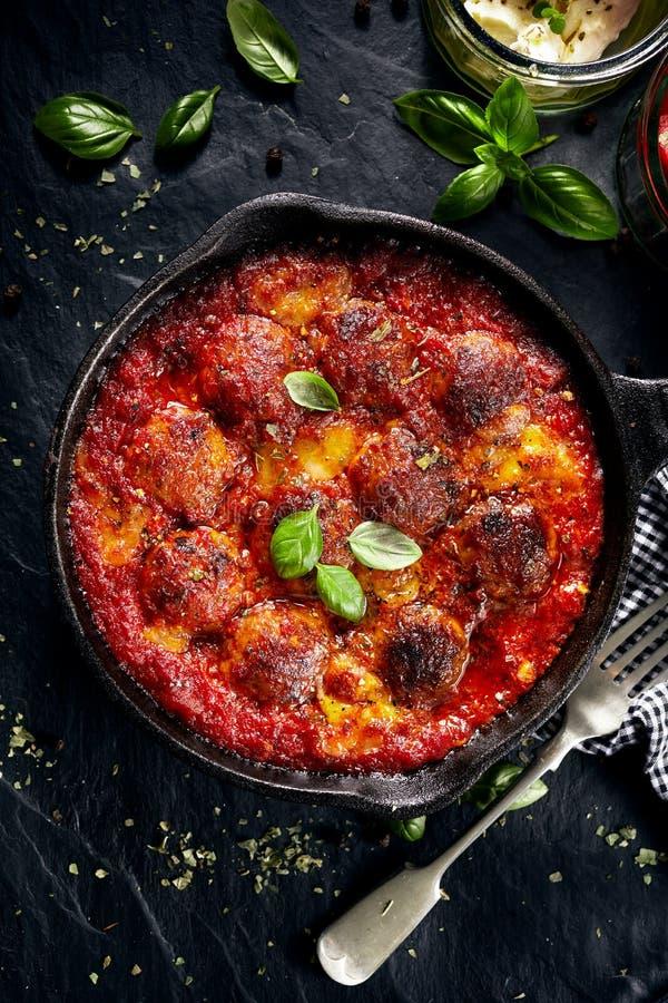Polpette in salsa al pomodoro con il formaggio della mozzarella dell'aggiunta ed in basilico fresco sulla pentola del ferro fotografia stock libera da diritti