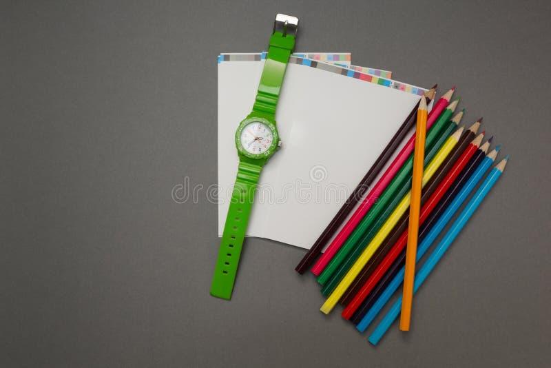 Polshorloge, een notitieboekje en een potlood op een grijze achtergrond royalty-vrije stock afbeelding