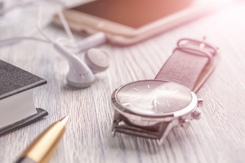 Polshorloge, mobiele telefoon met hoofdtelefoons en een notitieboekje met een pen op een oude witte bureaudesktop en een koffie stock foto