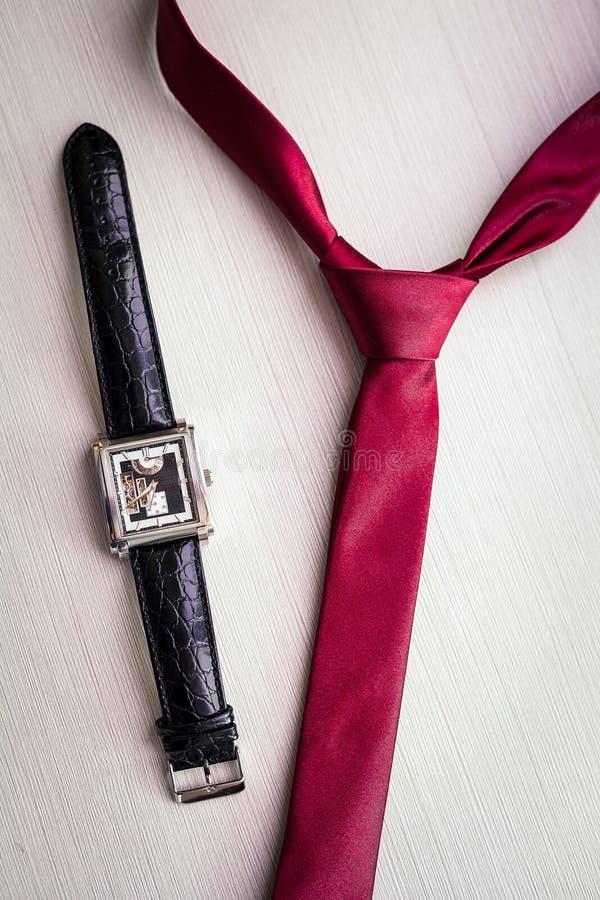 Polshorloges en rode band van de bruidegom stock foto