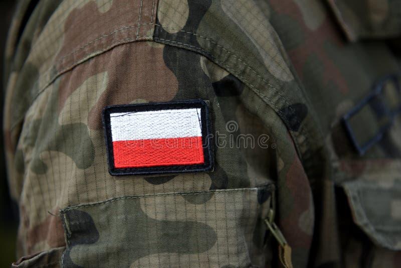 Polska łaty flaga na żołnierz ręce Polska wojskowy uniform Pole zdjęcia stock