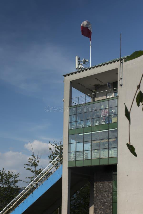 Polska czerwona flaga nad wierza narciarskiego doskakiwania wzgórze i biel zdjęcia stock