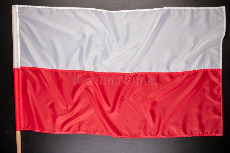 Polska flaga na ciemnym stole Flaga dołączająca drewniany dźwigar obraz stock