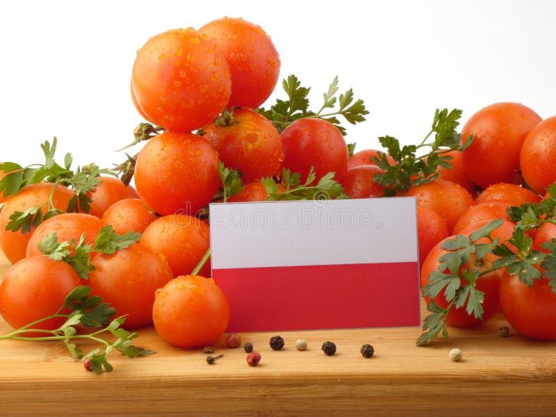 Polska flaga na drewnianym panelu z pomidorami odizolowywającymi na bielu zdjęcia stock