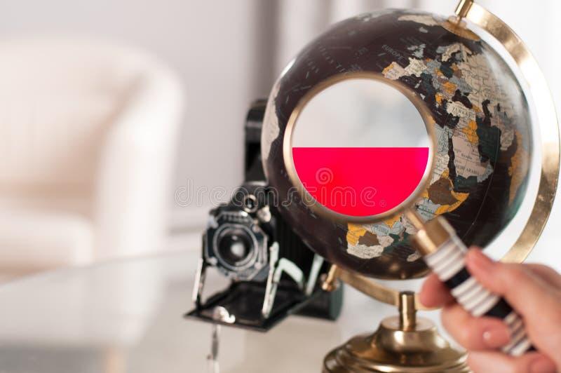 Polska flaga na kuli ziemskiej przez powiększać fotografia stock
