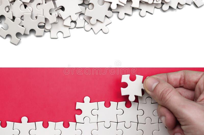 Polska flaga przedstawia na stole na którym składa łamigłówkę biały kolor ludzka ręka obraz stock