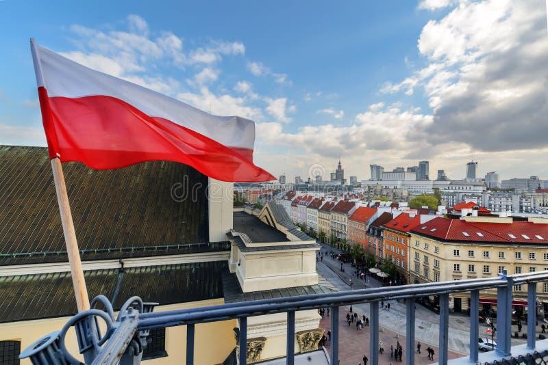Polska flaga w niebieskim niebie i Warszawa w tle obrazy stock