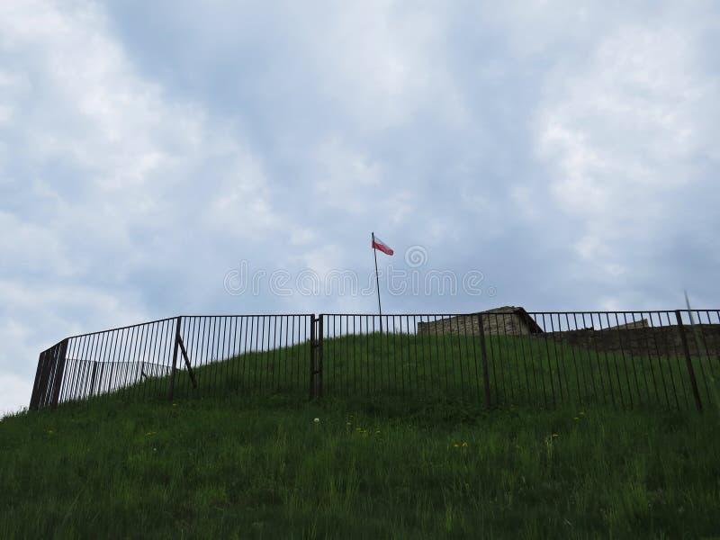 Polska flaga w wiatrze na wierza forteca z chmurami w tle obrazy royalty free