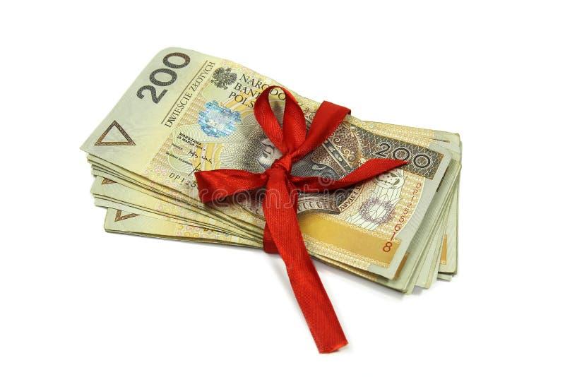 Polska pengarsedlar som binds med det röda bandet som isoleras på vit fotografering för bildbyråer