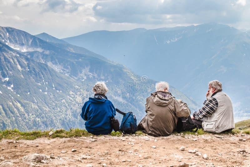 Polski Tatras Polska Czerwiec 3 2019: starsi ludzi z plecakami siedzą na zmielonej wysokości w górach Starego człowieka spojrzeni obraz stock