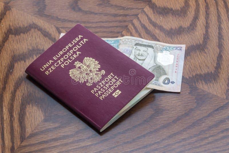 Polskt pass med 50 jordanska dinar på trätabellen fotografering för bildbyråer