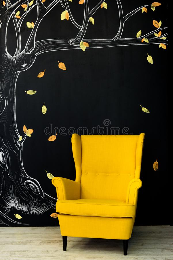 Poltrona amarela brilhante oposto a uma parede preta imagem de stock