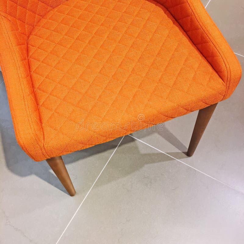 Poltrona arancio luminosa sulla pavimentazione in piastrelle fotografia stock