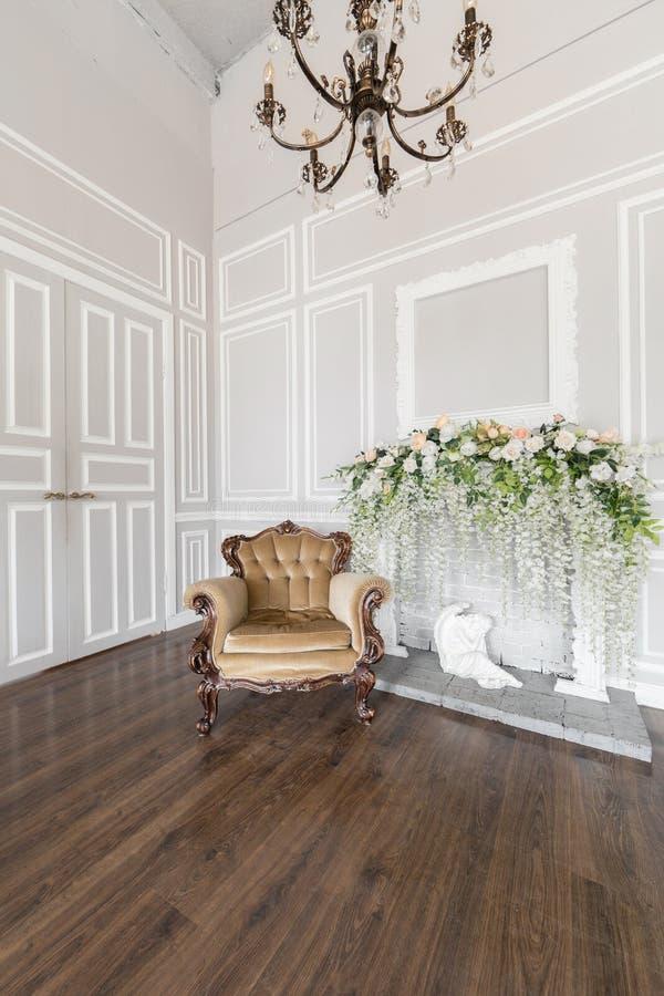 Poltrona beige Decorazione di stile della primavera Il camino bianco Interno di stanza luminosa nello stile di lusso reale classi immagine stock libera da diritti