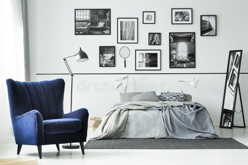 Poltrona blu comoda in camera da letto monocromatica interna con letto a due piazze e la galleria dei manifesti sulla parete fotografia stock libera da diritti