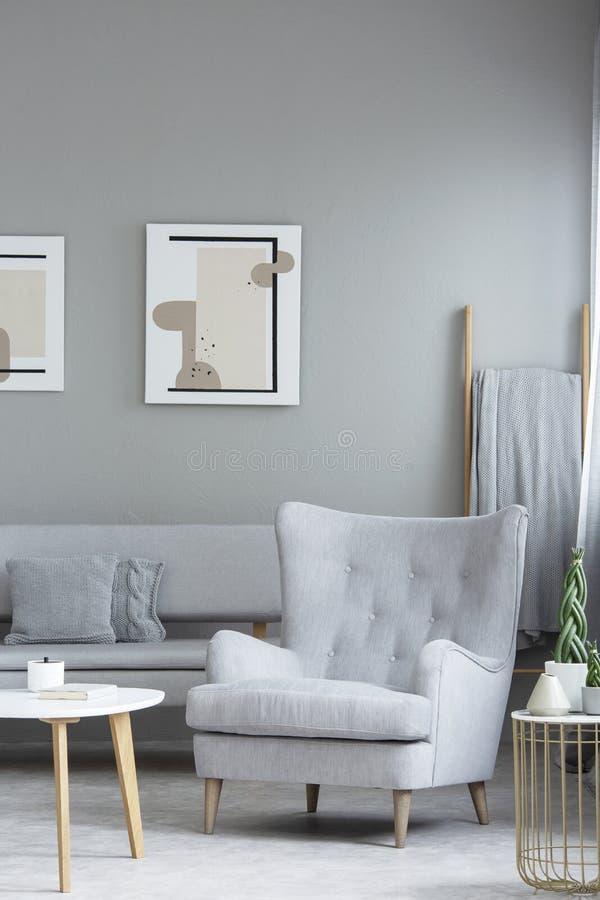 Poltrona cinzenta ao lado da tabela de madeira no interior da sala de visitas com imagens de stock