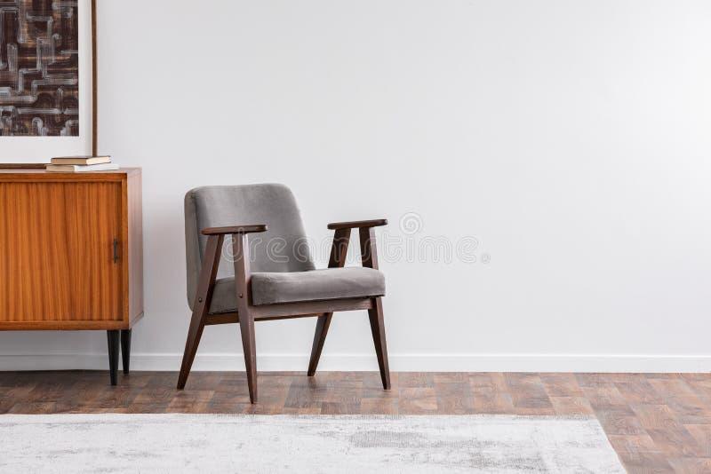 Poltrona do vintage do cinza ao lado do armário retro com livros, tapete morno no tolo de madeira, foto real fotografia de stock