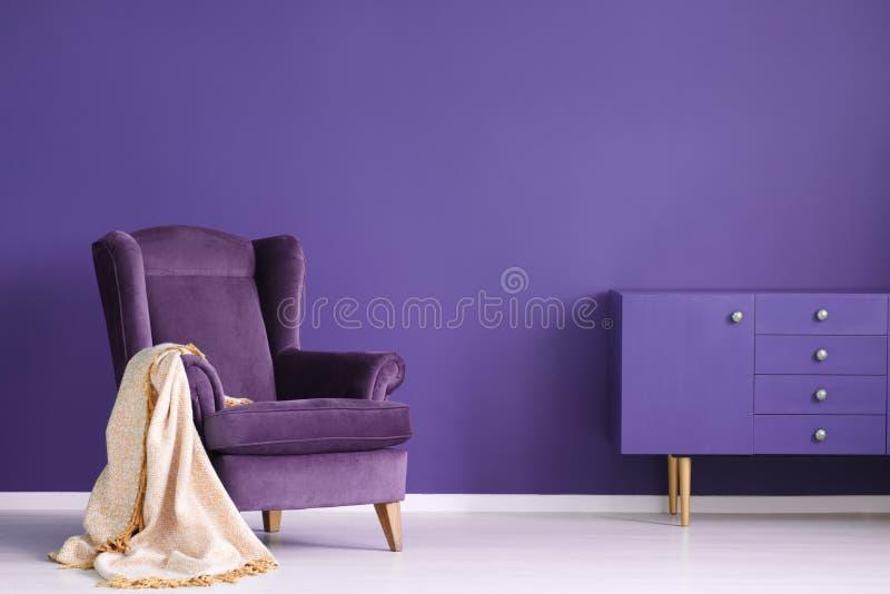 A poltrona do vintage, a cobertura bege e o armário ajustaram-se em uma parede violeta fotos de stock royalty free
