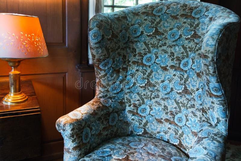 Poltrona do vintage e luz azuis do candeeiro de mesa imagem de stock royalty free