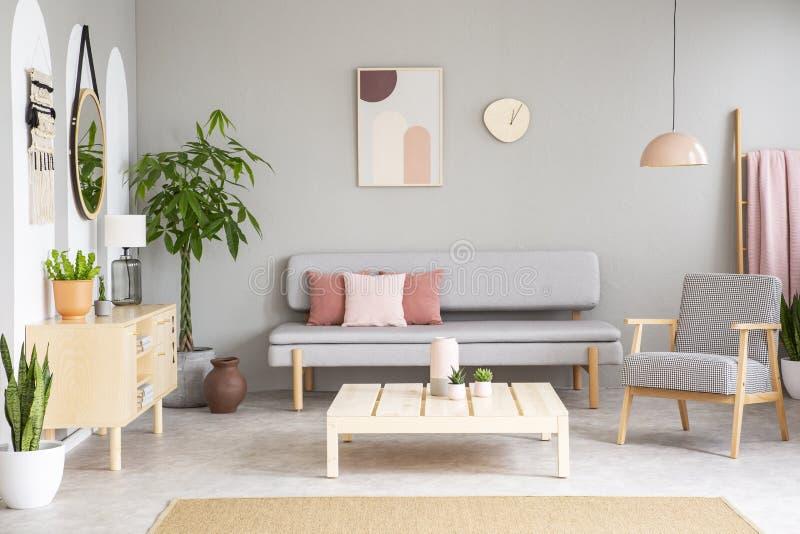Poltrona modelada ao lado da tabela de madeira em horizontalmente interior com pi imagens de stock royalty free