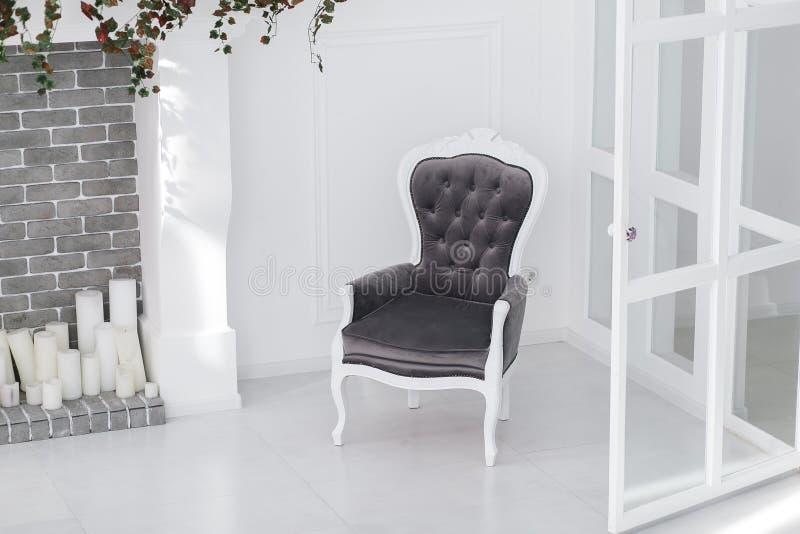 Poltrona preto e branco do vintage das veludinhas na sala escandinava minimalistic com chaminé e velas do tijolo horizontal imagem de stock royalty free