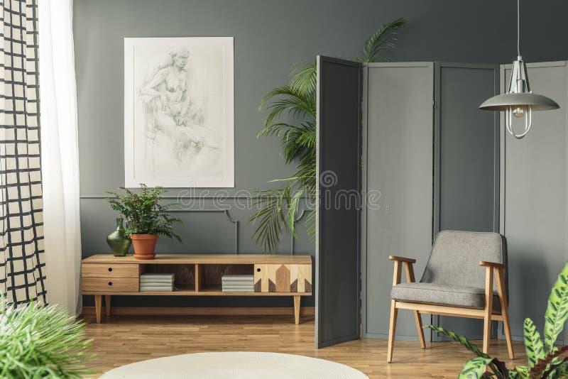 Poltrona retro contra uma tela cinzenta ao lado de um desenho que pendura o fotografia de stock royalty free