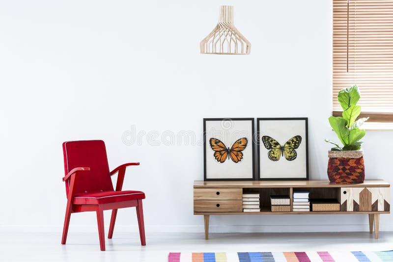 Poltrona rossa accanto ad un armadietto di legno con il manifesto della farfalla dentro fotografia stock libera da diritti