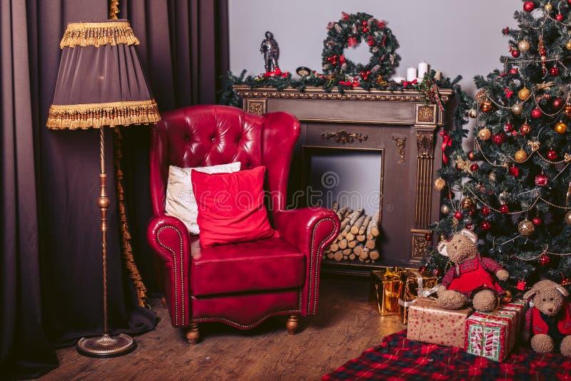 Poltrona vermelha em um estilo moderno no interior retro novo do ` s do ano com uma árvore de Natal, uma chaminé e as caixas de p fotografia de stock royalty free