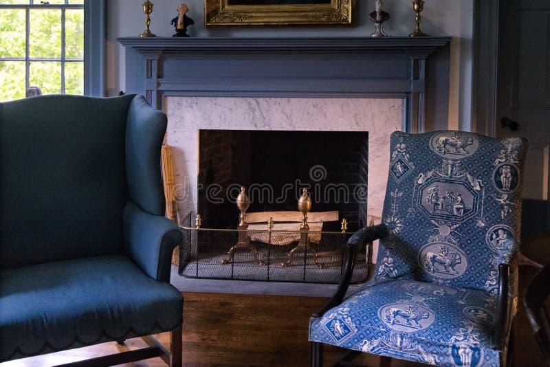 Poltronas azuis retros perto da chaminé do vintage com madeira do fogo fotos de stock royalty free
