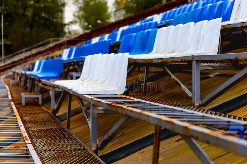 Poltronas brancas e azuis no pódio do estádio imagem de stock