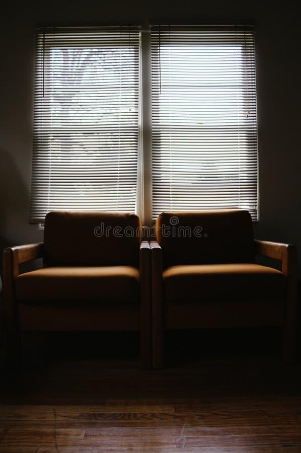 Poltrone accanto a ogni altro in una stanza scura con una grande finestra fotografia stock